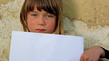 Boy holding a sheet of paper the background of an old wall.