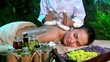 Woman getting thai herbal compress massage in spa.