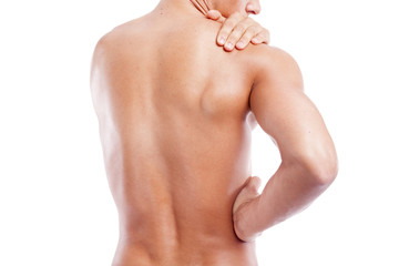 Muscular man holding his back and shoulder in pain, isolated on