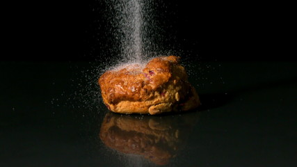 Sugar sprinkling on scone on black background