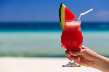 hand holding watermelon cocktail on the beach