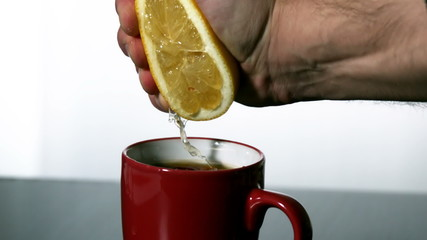 Man squeezing lemon into red mug