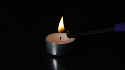 Lighter lighting a tealight candle