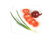 Spring onion and sliced tomato on the plate.