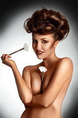 Lovely young adult brunette with brushes smiling at camera