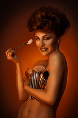 Charming girl smiling at camera with plurality of cosmetic brush