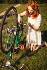 Red-hair woman repair a bicycle