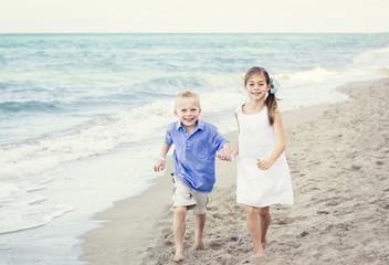 Children running together along the beach