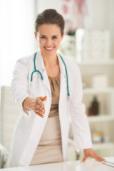 Closeup on medical doctor woman stretching hand for  handshake