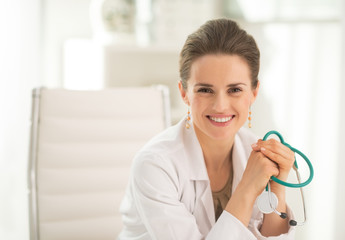 Portrait of smiling medical doctor woman sitting in office