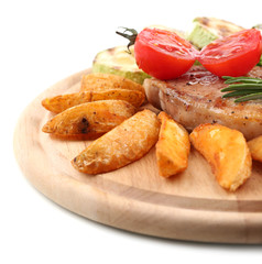 Grilled steak with fried potato pieces and grilled vegetables