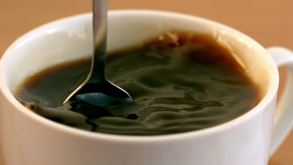 Teaspoon stirring coffee in a cup