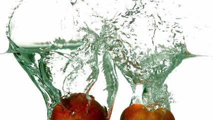 Apple halves plunging into water on white background
