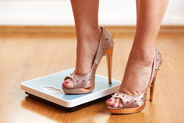 Female feet in golden stilettos with weight scale
