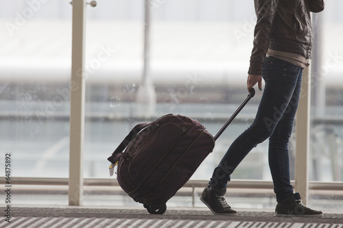 Woman carries your luggage at the airport terminal - 64875892