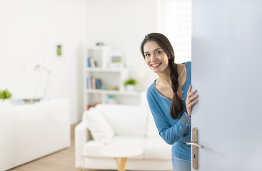 Cheerful woman inviting people to enter in home