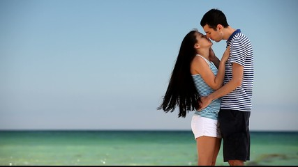 Young couple on the beach in summer day.
