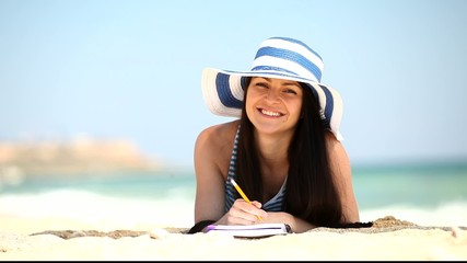 Young brunette girl with note and pencil on the beach in summer