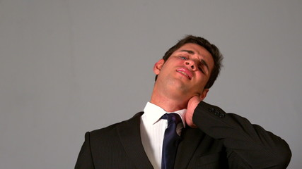 Businessman rubbing his sore neck