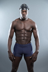 Athletic muscled black african swimmer wearing protective glasse