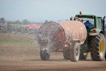 tractor con remolque regando pista de tierra antes de rally