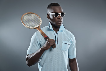 Retro black african tennis player wearing blue shirt and white s