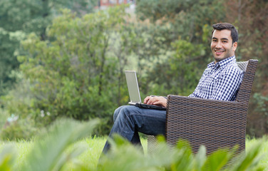 Smile young man with laptop, outdoor