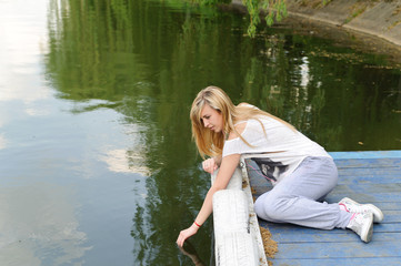 Young beautiful woman bent to the water