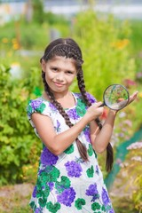 girl with magnifying glass and beetle