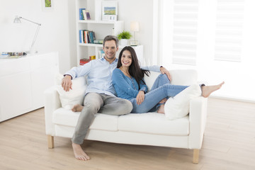 cheerful couple relaxing in sofa at home