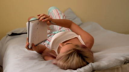 Pretty young blonde writing in notepad on her bed