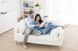 cheerful couple using digital tablet in sofa at home - 64881234