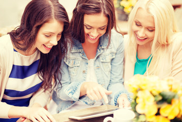 three beautiful girls looking at tablet pc in cafe