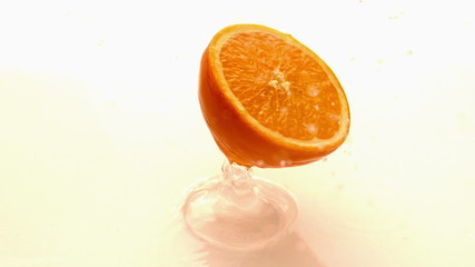 Orange half falling and bouncing on white wet surface