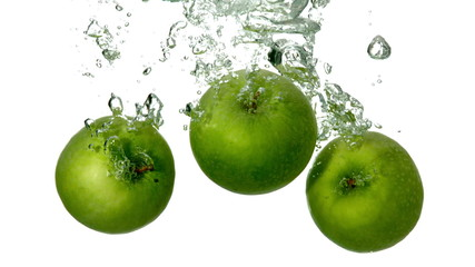 Green apples plunging into water on white background