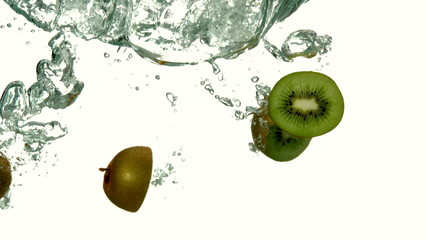 Kiwi pieces plunging into water on white background