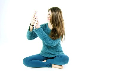 Cute teenager girl taking selfie picture of herself in studio