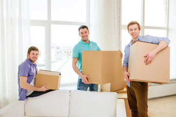 smiling male friends carrying boxes at new place