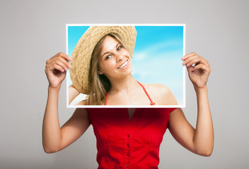 Woman holding a portrait of herself in a tropical beach