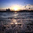 waves splashing on a beautiful sunset above Venice