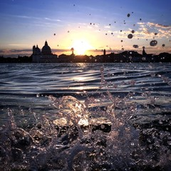 waves splashing on a beautiful sunset above Venice