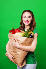 smiling woman holding a grocery bag full of fresh and healthy