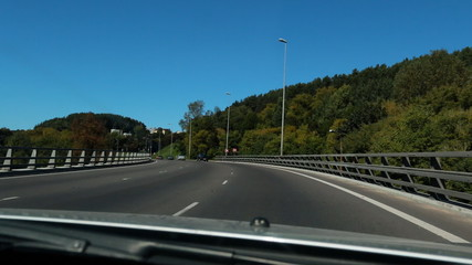 Car windscreen view of a motorway bridge