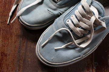 Old blue canvas shoe on wooden floor.