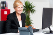 Cheerful aged woman working at the desk