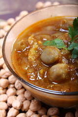 close up of indian spicy chana masala with raw chickpeas around