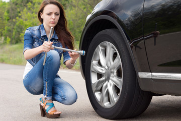 Confused woman looking at a wheel spanner