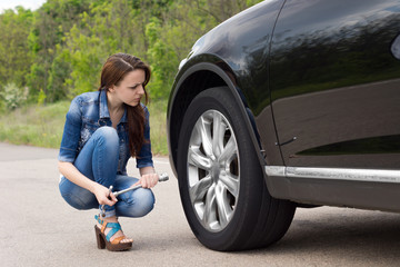 Young woman checking out a flat tyre on her car