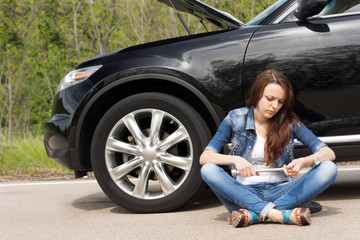 Woman waiting beside her broken down car