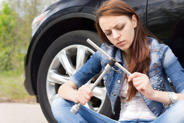 Ignorant woman frowning at a wheel spanner